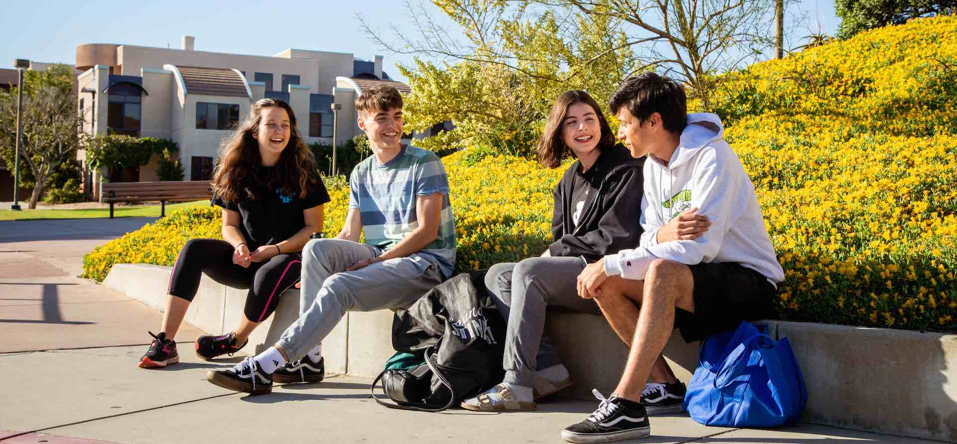four students sitting outdoors smiling and interacting