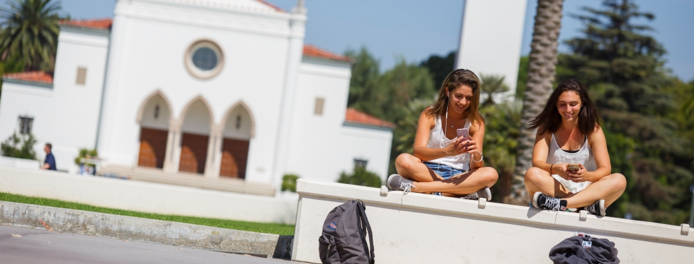 Two students text on their phones in front of LMU's Sacred Heart Chapel.