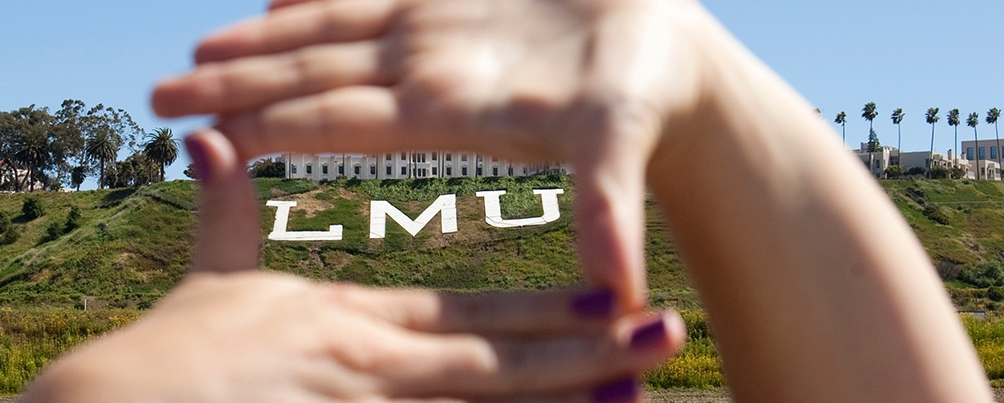A student frames the Loyola Marymount University bluff letters in between his hands.