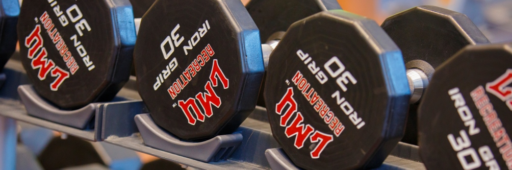 Free weights with Loyola Marymount University's logo sit at the Burns Recreation Center on campus.